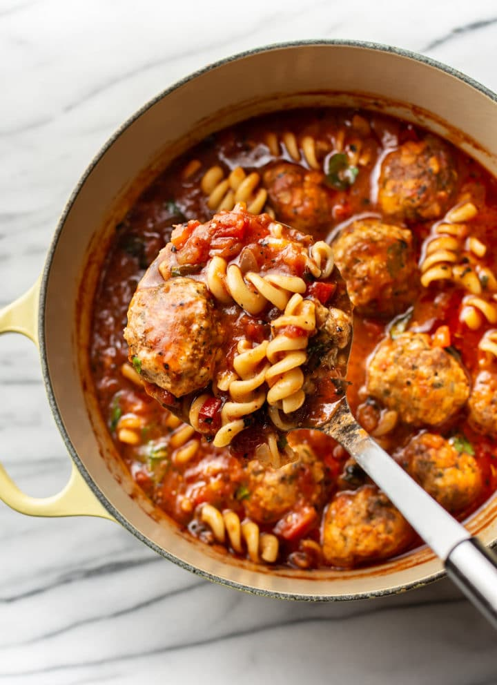 meatball soup in a pot with a ladle full