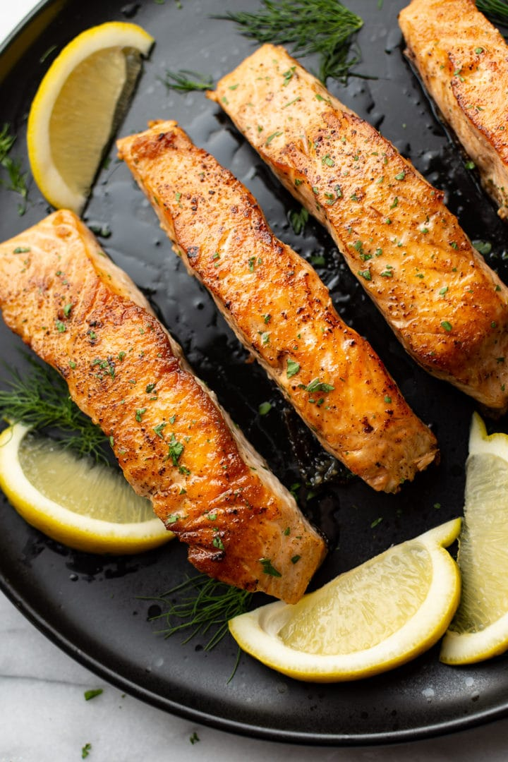pan seared salmon on a black plate surrounded by lemon wedges