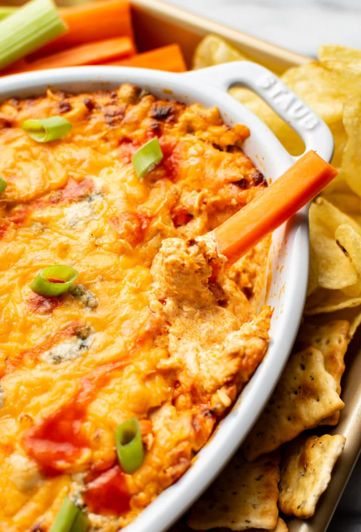 a carrot being dipped into easy buffalo chicken dip