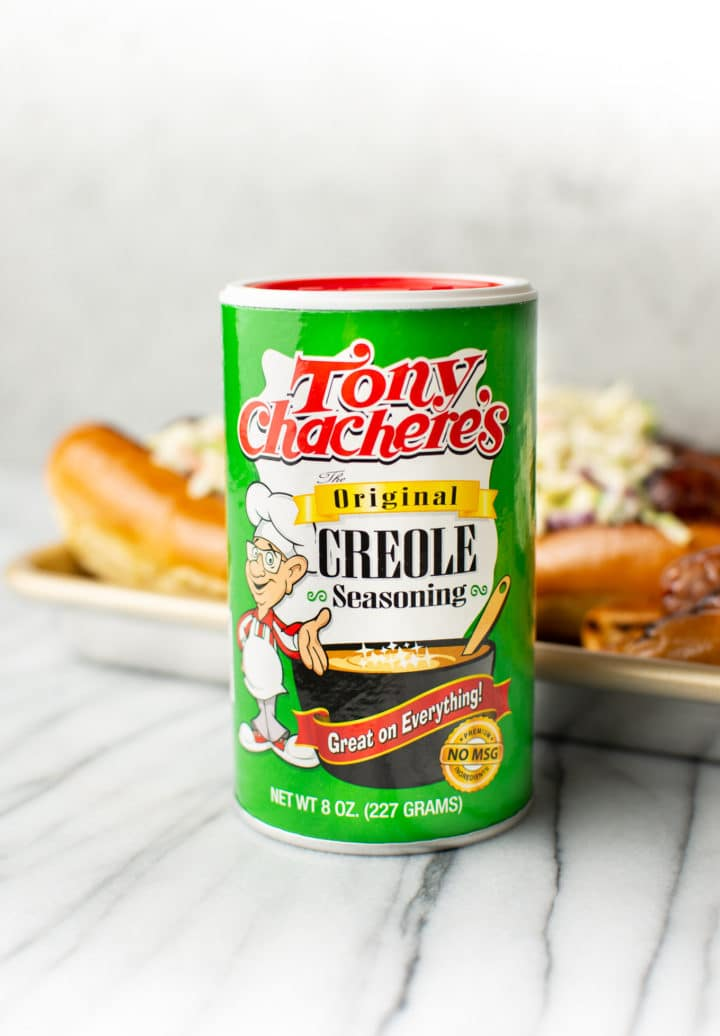Tony Chachere's Original Creole Seasoning in foreground with a tray of Cajun beer brats in the background