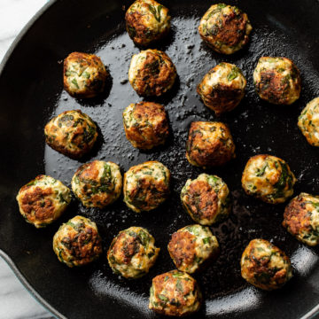 skillet filled with chicken spinach meatballs