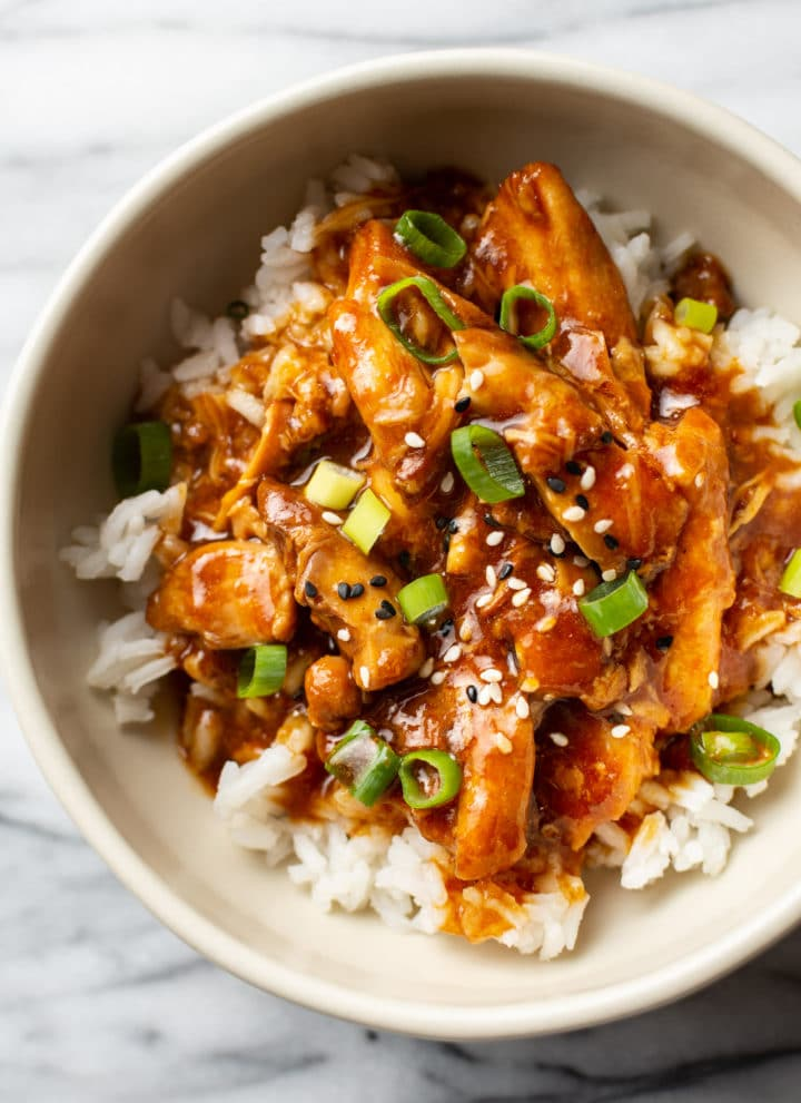 honey garlic slow cooker chicken thighs in a bowl, served over rice and topped with scallions and sesame seeds