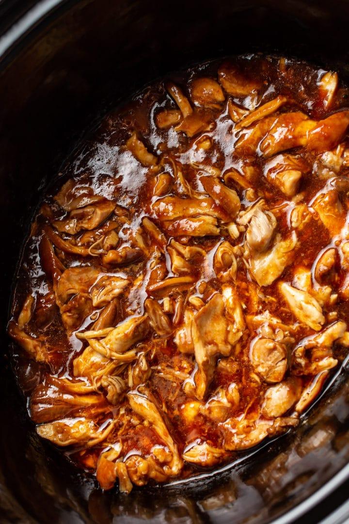 close-up of honey garlic slow cooker chicken thighs shredded in Crockpot