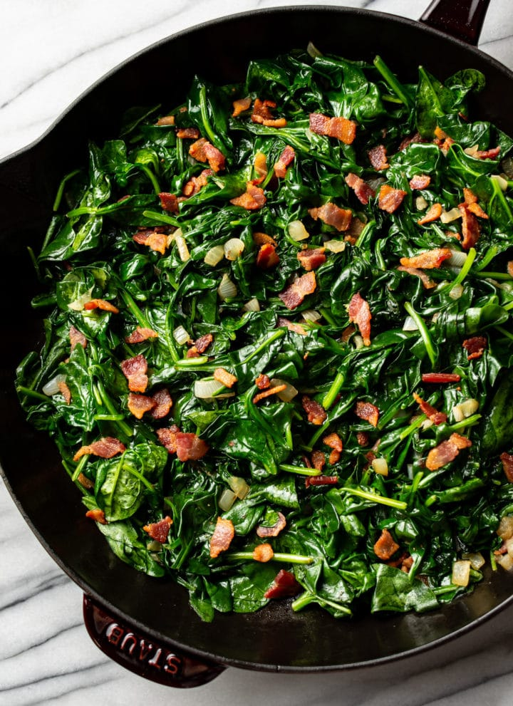 sautéed spinach with bacon in a cast iron skillet