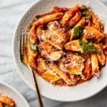spicy chicken pasta in two shallow bowls