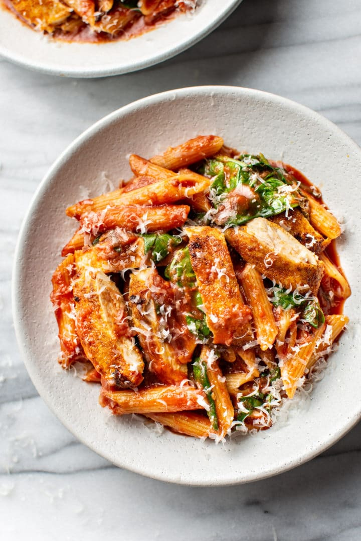 close-up of spicy chicken pasta with penne in a shallow bowl
