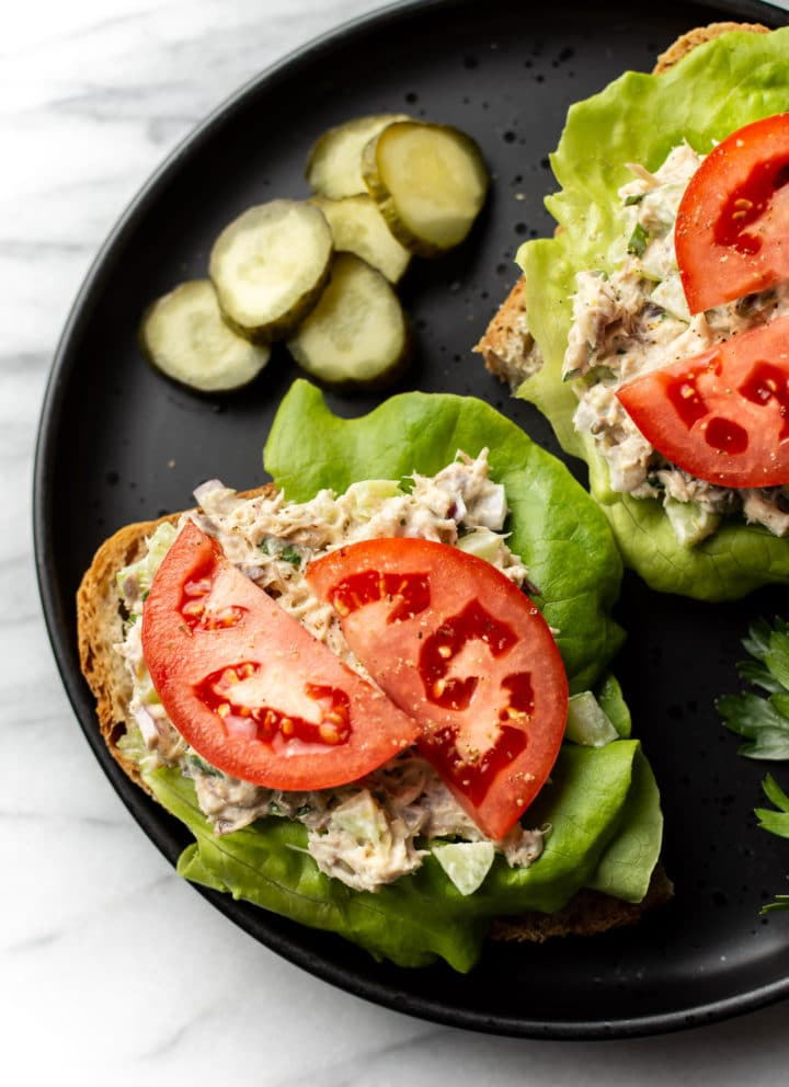 canned mackerel salad on open faced sandwiches with lettuce and tomato on a plate