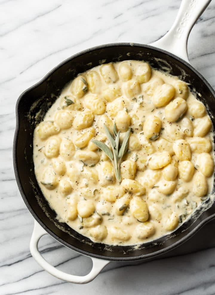 creamy sage gnocchi in a white Le Creuset skillet