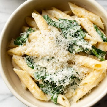 close-up of creamy spinach pasta in a beige bowl