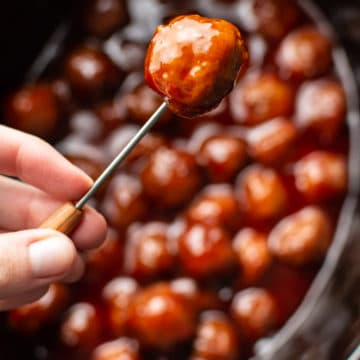 grape jelly meatball being held up on a cocktail toothpick