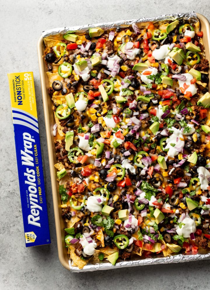 loaded sheet pan nachos topped to perfection with sour cream, fresh tomatoes, avocado, etc.