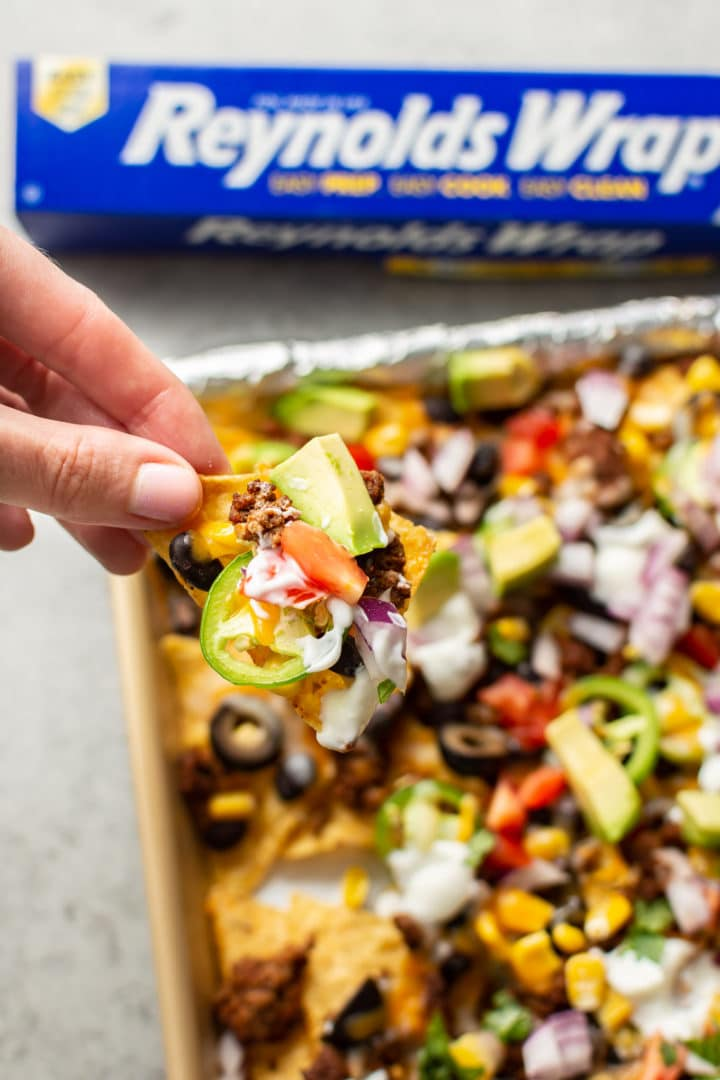 close-up of a female hand grabbing a nacho