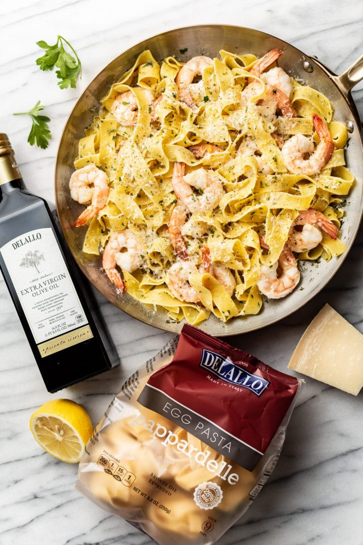 pappardelle with shrimp surrounded by a package of DeLallo's Egg Pappardelle and Private Reserve Olive Oil